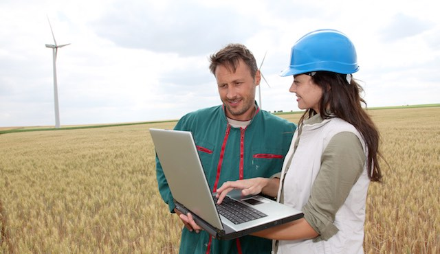 Man and Woman In Field With Laptop